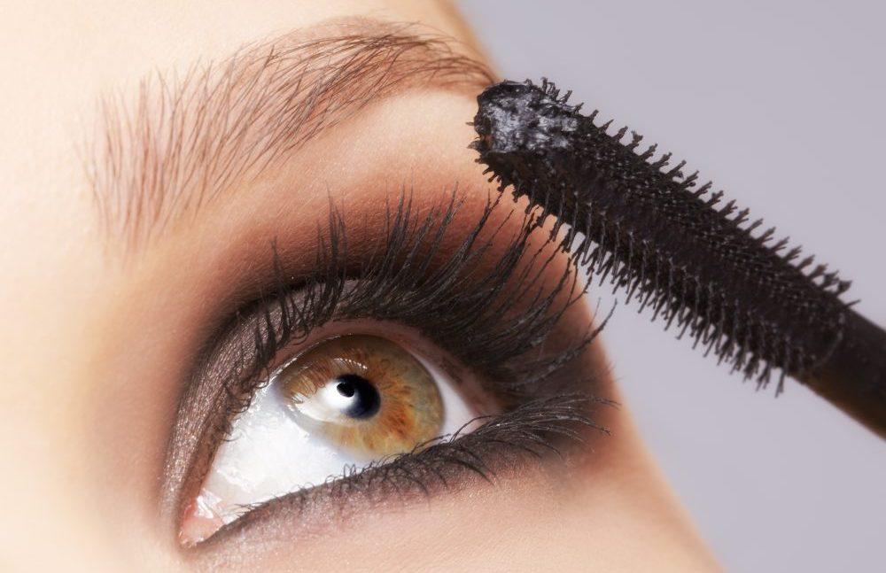 close up portrait of beautiful young brunette woman applying mascara